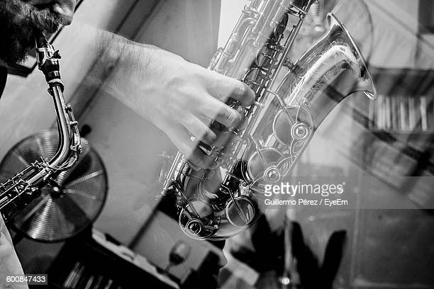 Double Exposure Of Man Playing Saxophone And Glass On Table