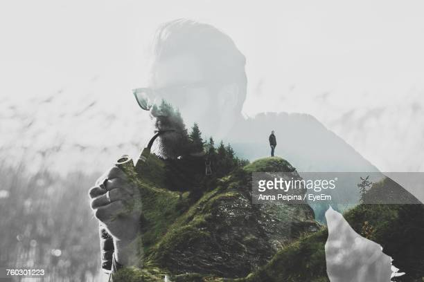 double exposure of man smoking and female hiker standing on mountain - mehrfachbelichtung stock-fotos und bilder