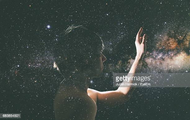 Double Exposure Of Man Touching Starry Sky