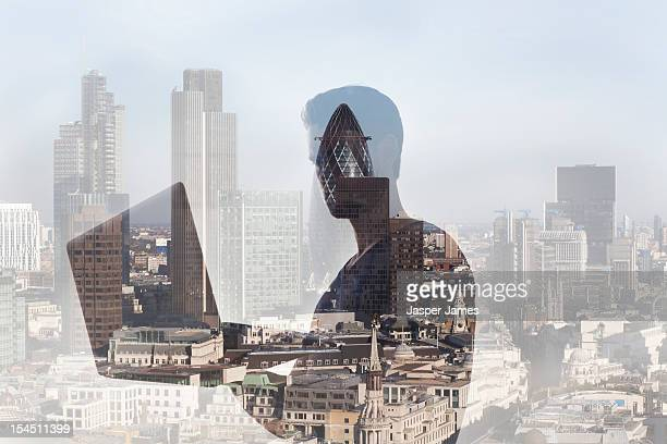 double exposure of man using laptop and cityscape