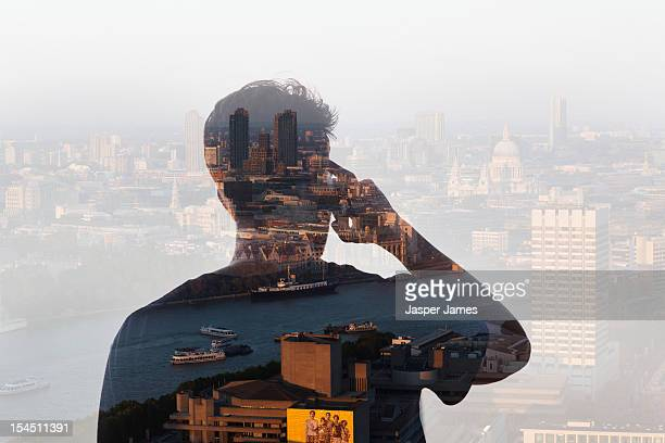 double exposure of man using phone and cityscape