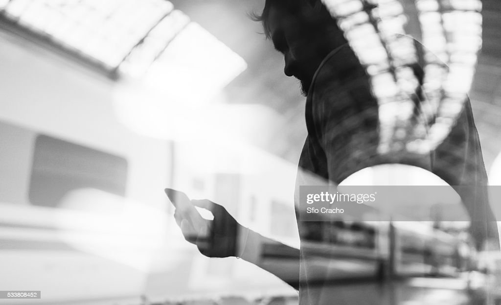 Double exposure of man using phone and train station : Foto stock