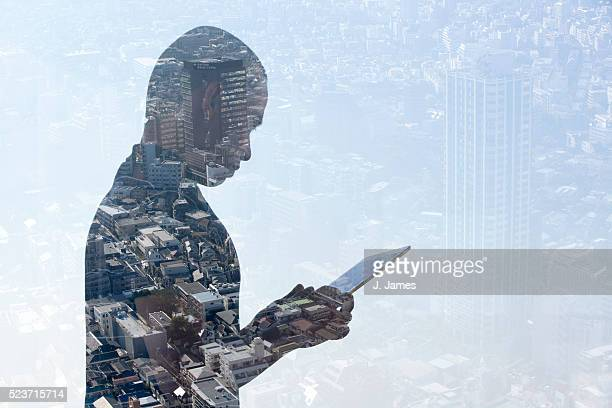 Double exposure of man using iPad and cityscape
