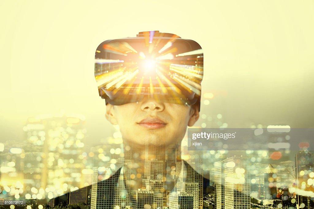Double exposure of man wearing virtual reality headset : Stock Photo