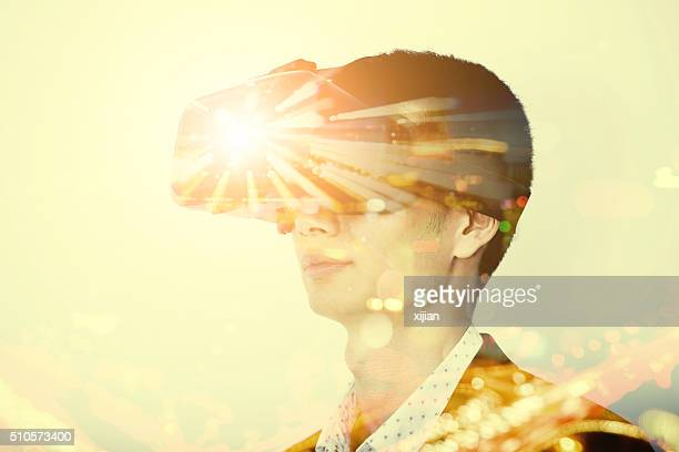 Double exposure of man wearing virtual reality headset
