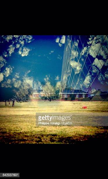 Double Exposure Of Modern Building And Field Against Sky