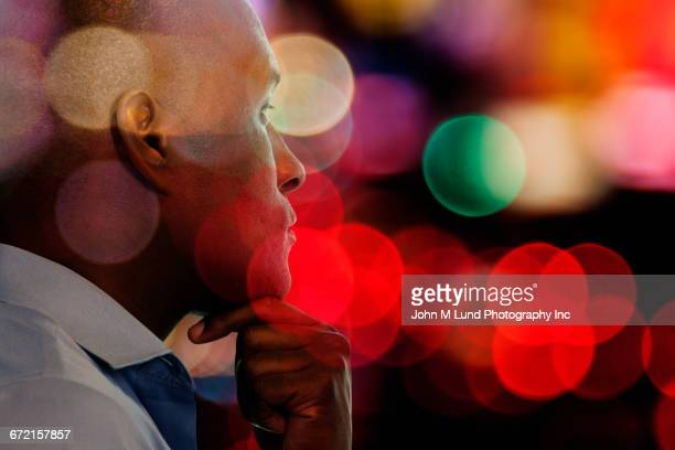 Double exposure of pensive Black businessman and multicolor circles
