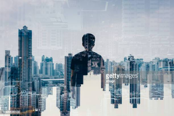 double exposure of rear view smart young man against aerial view of hong kong city skyline - multiple exposure stock pictures, royalty-free photos & images