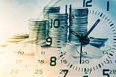 double exposure of rows of coins with clock and calendar for business and finance background