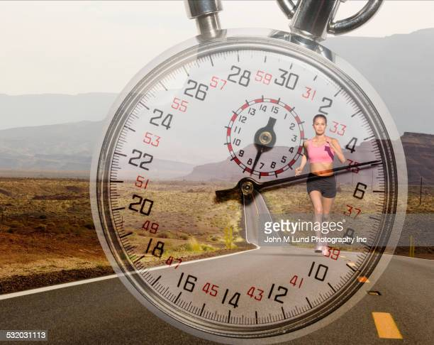 Double exposure of runner on remote road over stopwatch