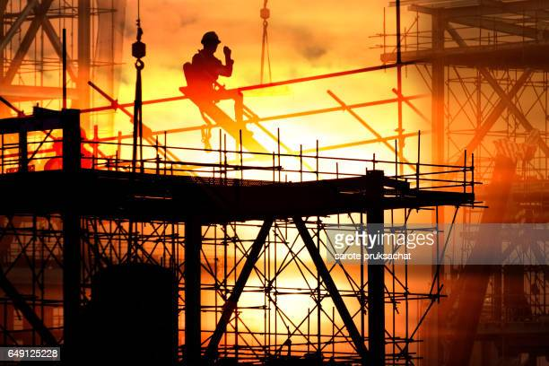 Double exposure of silhouette construction site .