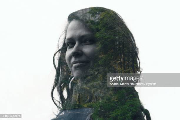 double exposure of smiling young woman and forest against white background - multiple exposure stock pictures, royalty-free photos & images