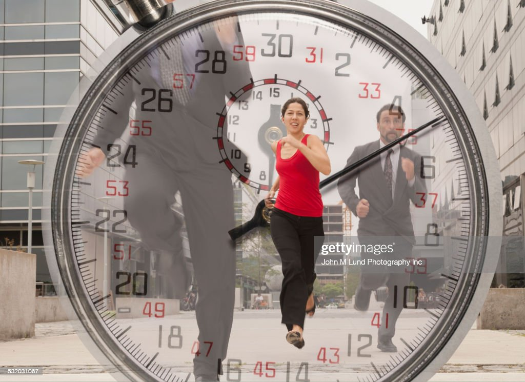 Double exposure of stopwatch and business people running outdoors : Stock Photo