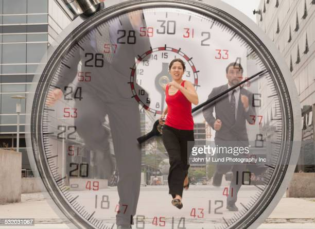 Double exposure of stopwatch and business people running outdoors