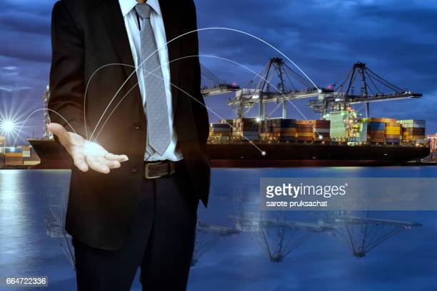Double exposure of success businessman show his hand to success concept and Logistic Import Export background , Management concept .