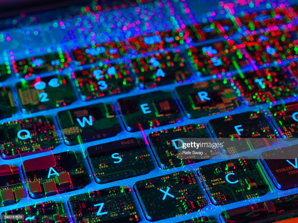 Double exposure of the inside and out of a laptop computer showing the electronic components under the keyboard : Stock Photo