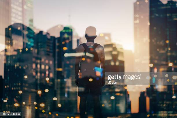double exposure of urban illuminated cityscape and rear view of man overlooking at city - weisheit stock-fotos und bilder