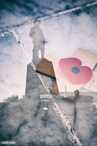 Double exposure of war memorial and Anzac poppy on a cross