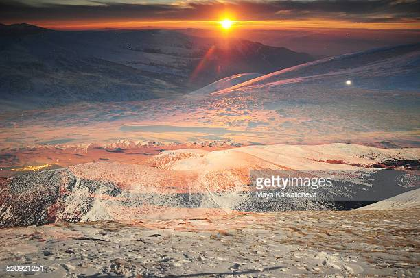 Double exposure of winter sunset in snowy mountain