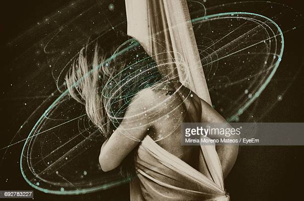 Double Exposure Of Woman Covering With Fabric And Light Trails Against Black Background