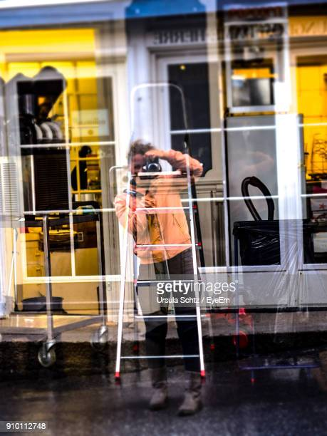 Double Exposure Of Woman Photographing And Building