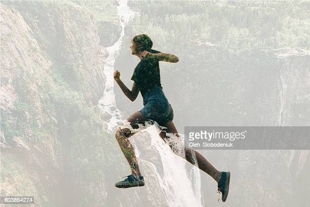 Double exposure of woman running and waterfall