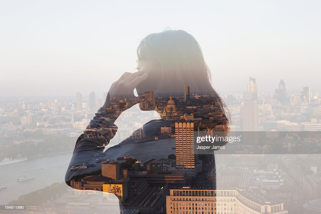 double exposure of woman using phone and cityscape : Foto de stock