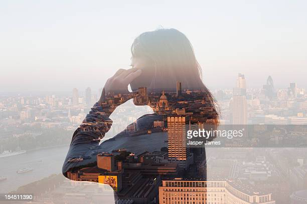double exposure of woman using phone and cityscape
