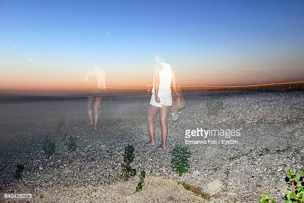 Double Exposure Of Women Walking On Field Against Sky During Sunset