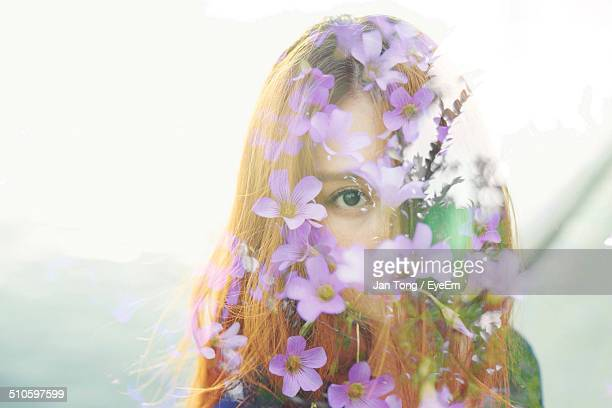 Double exposure of young woman surrounded by purple flowers
