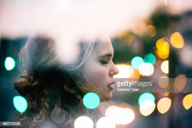 Double exposure of young woman with bokeh city lights.