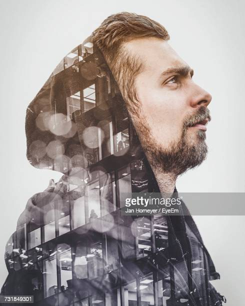 Double Exposure On Man Wearing Hooded Shirt And Buildings Against White Backgroundd