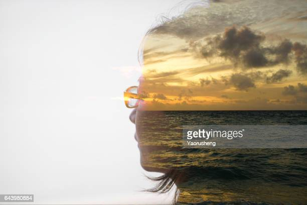 Double exposure portrait of a woman with sunset ocean background
