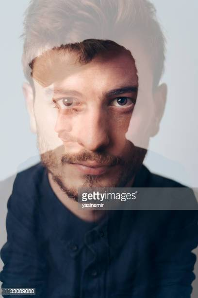double exposure portrait of a young male looking at camera in the studio. multiple exposure self portrait - serene people stock pictures, royalty-free photos & images