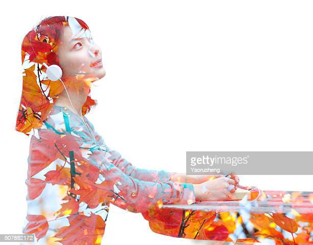 Double exposure portrait of young woman covered by yellow leaf,China