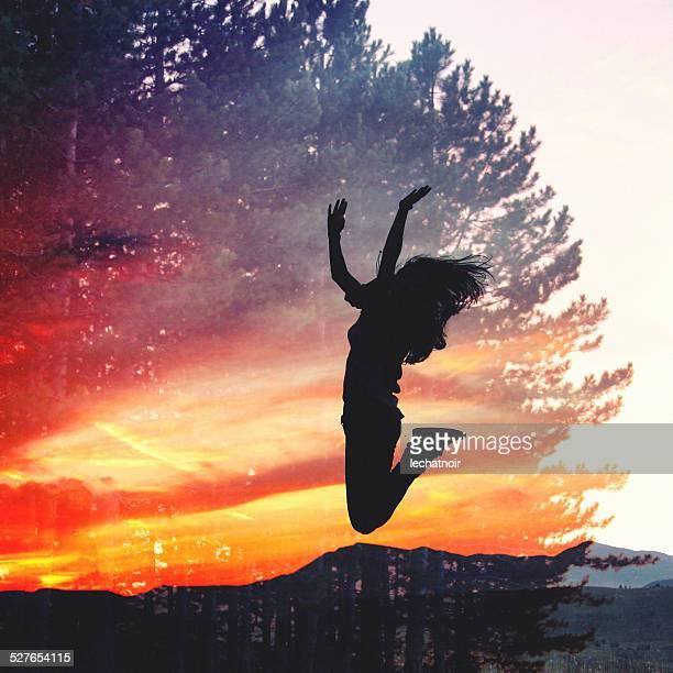 Double exposition silhouette d'une jeune fille sauter contre le coucher de soleil
