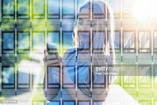 Double exposure: Young woman using smart phone