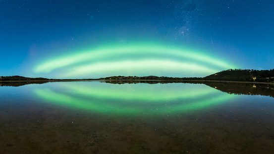 Double green arc of Aurora with reflection in water at blue hour - gettyimageskorea