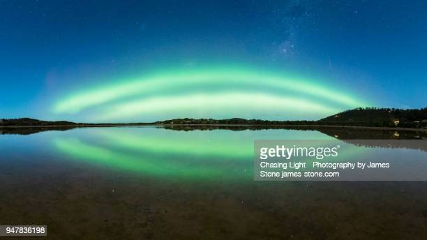 double green arc of aurora with reflection in water at blue hour - aurora australis stock pictures, royalty-free photos & images