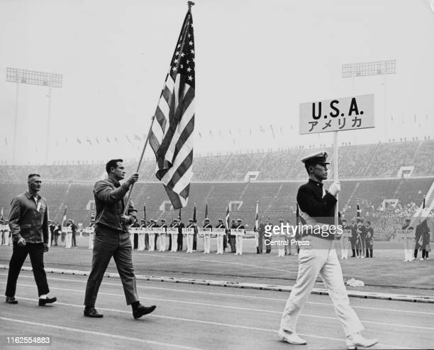 Double Olympic gold medalist in the shot put competition Parry O'Brien of the United States carries the stars and stripes national flag during the...
