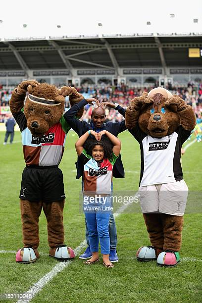 Double Olympic gold medalist Mo Farah and daughter Rihanna Farah pose with the Harlequins mascots during the Aviva Premiership match between...