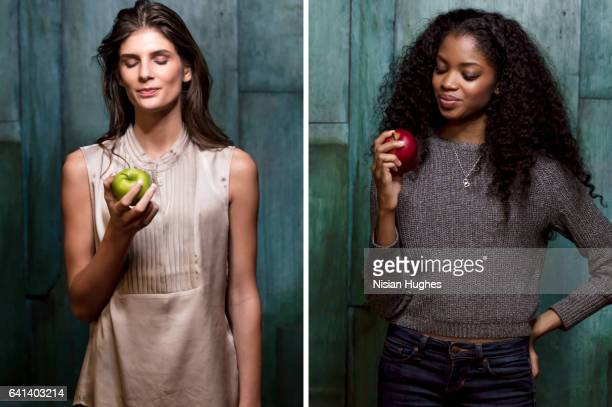 Double portrait of two young women eating apples
