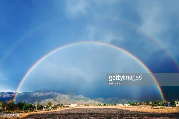 double rainbow after a storm, with sandia mountains in background - sandia mountains stock pictures, royalty-free photos & images