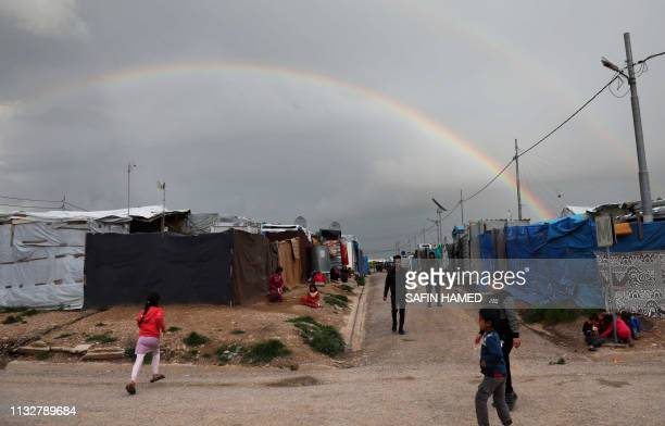 TOPSHOT A double rainbow colours the sky as displaced Iraqi children who fled their homes along with their families due to attacks by the Islamic...