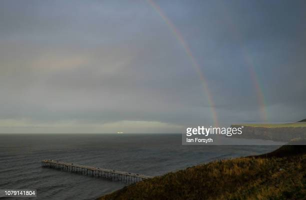 A double rainbow forms over the pier and cliffs on December 8 2018 at SaltburnbytheSea England Showers are expected to continue to spread eastwards...