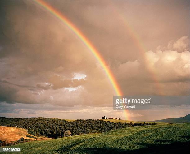Double rainbow over chapel on a hillside