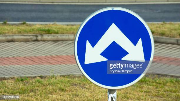 Double way road sign with white arrows on blue circle