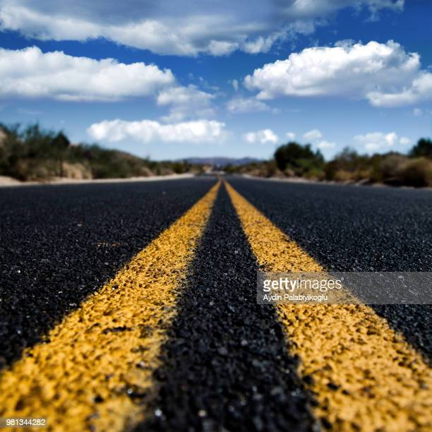 double yellow line on empty road through desert, palm springs, joshua tree national park, california, usa - double yellow line stock photos and pictures