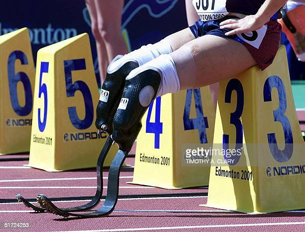 A doubleamputee competitor sits on a lane marker preparing to compete in the women's 100M amputee final at the 8th World Championships in Athletics...