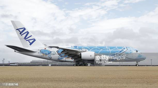 A doubledeck Airbus A380 plane featuring a turtle face design arrives at Narita airport near Tokyo on March 21 from France for All Nippon Airways to...